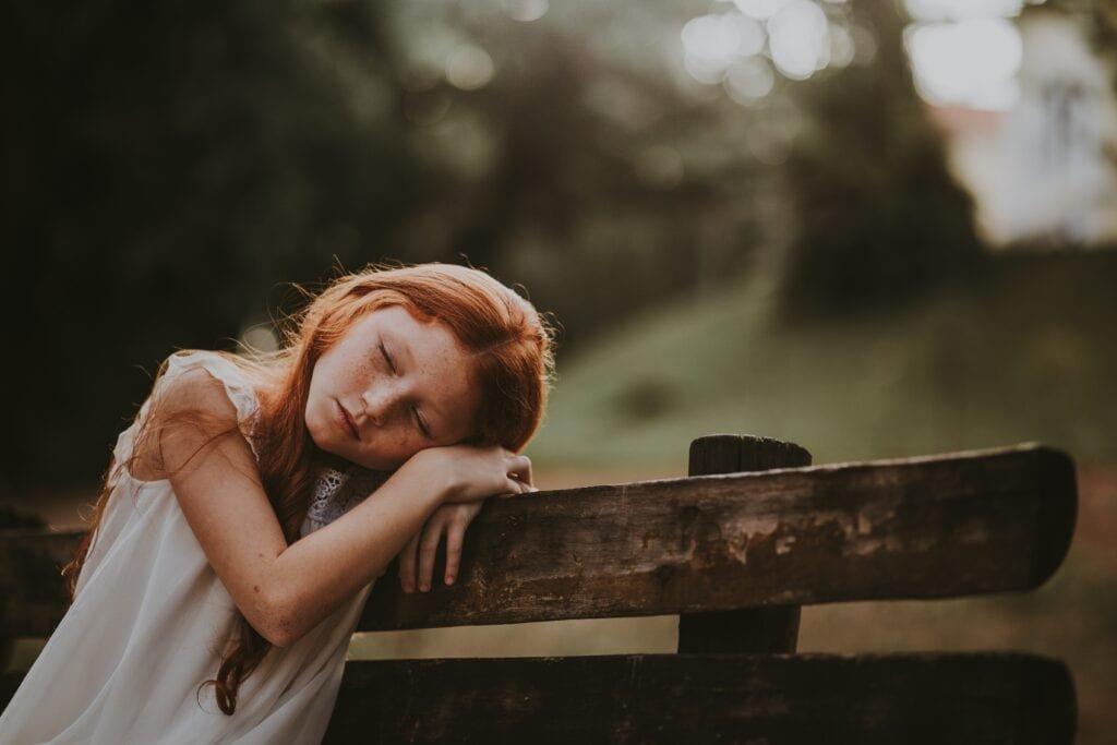 Mädchen schläft auf der Bank ein