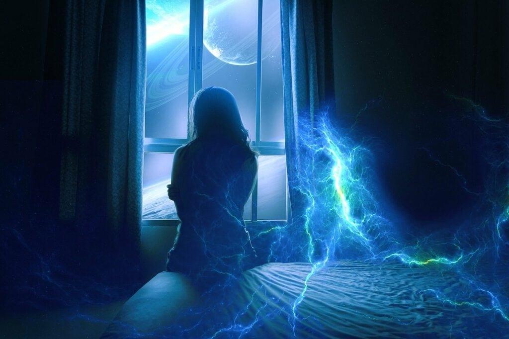 Frau sitzt am Fenster, ihre Aura schimmert blau