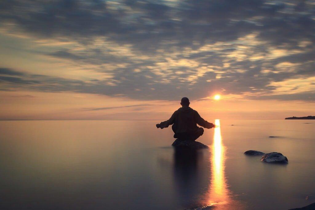Meditierender Mönch am Strand bei Sonnenuntergang