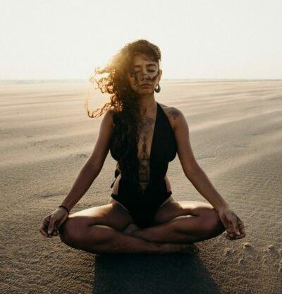 meditierende frau sitzend auf einer düne