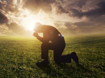Ein Mann betet unter freiem Himmel
