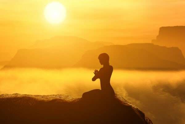 Frau meditiert bei sonnenuntergang